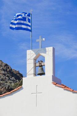 Weißer Kapellenturm mit Glocke vor einem Berg und wehender Griechenland Flagge