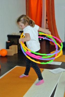 Ein Mädchen stellt im Kinderyoga mit mehreren Hula Reifen das schlüpfen aus dem Ei nach