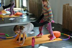 Zwei Mädchen haben Spaß zusammen die Turnübung Schubkarre auszuprobieren.