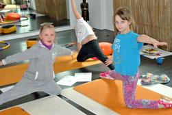 Im Kinderyoga finden drei Mädchen eine schöne Übung, die zeigt wie ein Küken aus dem Ei schlüpft.