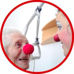 Eine Bewohnerin eines Seniorenheims lacht die Clownin Angelina Haug an und trägt dabei selber eine Clownsnase