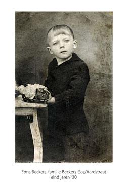 Jongetje aan een oude tafel met bloemen erop. Studiofoto.