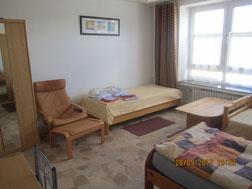 Großes Schafzimmer mit großem Tisch (nicht sichtbar) und Stühlen. 2 Kleiderschränke. 3 Einzelbetten. Ein weiteres Bett kann aufgestellt werden.