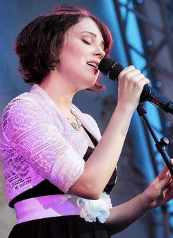 Sängerin Juli singt mit Mikrofon in der Hand beim Talentwettbewerb von Charivari