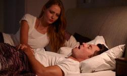 schnarchender Mann mit entsetzter Frau im Bett
