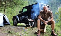 Mann sitzt vor Zelt und Jeep