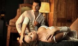 Mann steht hinter einer sehr attraktiven Frau