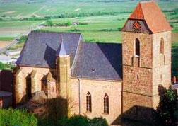 Eine ehemalige Burgkapelle aus Backstein mit rotem Turmdach und blau-grauem Kirchenschiffdach. Rundherum sind grüne Wiesen und Wälder zu sehen.