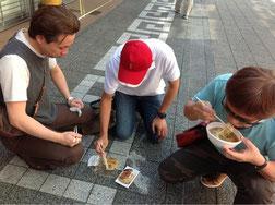 地べたに座って食する塾長たち!食べ歩きは面白い!