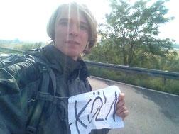 Trampen Mann Köln Pappe Papier Schild an Straße