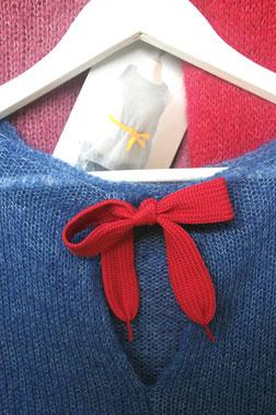 Nackenbereich eines blauen Oberteils mit roter Schleife auf Bügel, dahinter pinker und roter Strickartikel und Etikett mit Bild von Sommeroberteil