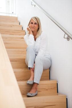 Kerstin Schmetzer sitzt auf Treppe und ist nach ihrer Ausbildung an der Coaching Akademy Berlin bereit für neue Klienten