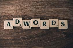 Scrabble-Steine welche das Wort Adwords zeigen. Hier geht es um das Angebot von Google Ads, welche früher Google Adwords hiessen.