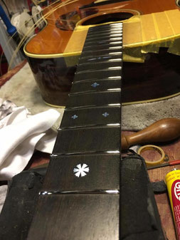 やすりがけが終了したギターネックに取り付けられたステンレスフレット