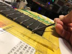 ギターのネックに新しいステンレスフレットをつけている作業