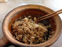 Hier sieht man schon gut, wie beim halb leergegessenen Reistopf der Reis immer knuspriger wird. Denn der Tontopf war ja schließlich sehr heiß beim Servieren.