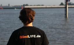 Erdin ist mit dem Rücken zur Kamera gedreht. Blick aufs Elbwasser, welches auch auf dem Bild zu erkennen ist. Ganz weit im Horizont sieht man Gebäude und davor ragt aus dem Wasser ein Pfosten heraus.