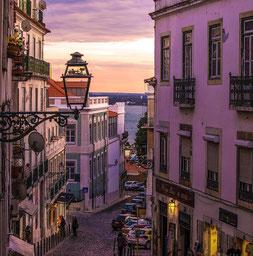 Lissabon in Abenstimmung - schmale Gasse im Abendlicht mit Blick auf das Wasser