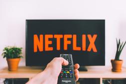Hand met afstandbedining die naar tv wijst waarop Netflix te zien is