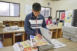 【写真】朝刊の配達準備で新聞に折込広告を挟み込んでいるところ