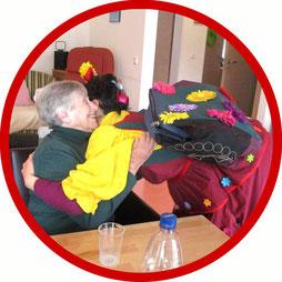 Die Bewohnerin eines Seniorenstifts freut sich sehr über die Umarmung der Klinik-Clownin
