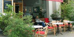 Eine junge Frau geniesst die Sonne bei Kaffee und Kuchen. Café beim Savignyplatz. Foto: Helga Karl