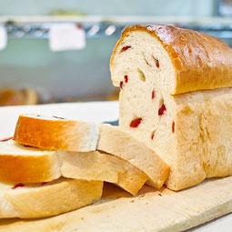 クランベリーブレッド。甘酸っぱい真っ赤なクランベリーがたっぷり入って、見た目も歯ごたえも楽しいパン。  7大アレルゲン 小麦、卵 1本¥450/ハーフ¥240