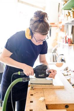 Frau mit Oberfräse an Werkbank in Holzwerkstatt