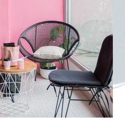 Zwei freie Stühle vor einer rosa farbigen Wand