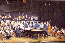 """""""Mozart meets Metallica"""": Pianisten und Teile des Orchesters beim abschliesenden Song  """"Halleluja"""". Rechts im Hintergrund der mitsingende Dirigent Marcin Grabosz.  Foto: Paul Krahe"""