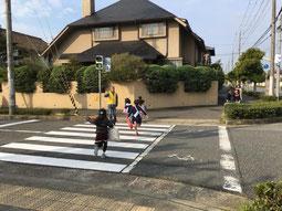 信号を渡る子どもたちと安全を見守っている大人の写真