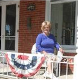 Anna VanDeventer sits on the mansion's porch. — Gary Brower/The Holland Sentinel