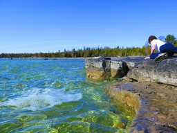 South shore of Lake Huron with boy looking at rocks.