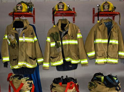 Row of firefighting jackets, helmets, and gear