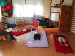 Kinder auf Matratzen am Boden liegend, betreut von einer Ergotherapeutin, bei einer Übung im Rahmen des Marburger Konzentrationstrainings.