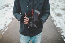 Mann mit professioneller Kamera. Er steht für die Videoproduktionen, die marketing-helper anbietet.