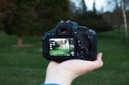 Eine Professionelle Kamera, welche ins Grüne zeigt. Sie steht für die Fotos und auch für die Grafiken, die marketing-helper für professionellen Content bietet.
