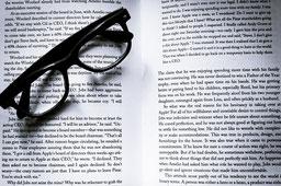 Eine Brille auf einem Buch, welche für professionelle Texte steht.