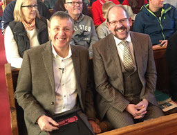 Nick Swanson and Phil Robinson sitting together in the congregation of a morning service at WBC