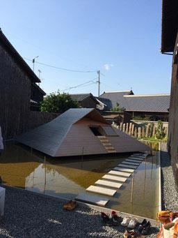 池の上で回転する民家『風と水のコックピット』