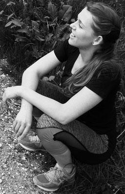 Entspannt lachende Frau im Hocksitz