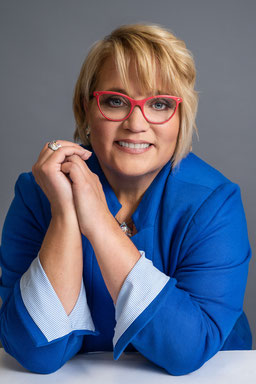 Click to go to headshot page. photo of woman posed holding eye glasses for a three quarter headshot.