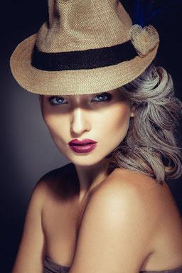 Eine junge Frau mit bereits ergrauten Haaren, Kuba-Strohhut und dunkelrotem Lippenstift im Portrait.