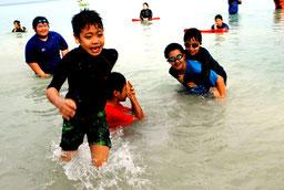 初泳ぎで海に駆け込み、はしゃぐ子どもたち=17日午前、底地ビーチ