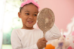 Photo of a little girl admiring her princess tiara in a silver mirror