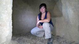 """Abbildung: Anita in einer der """"Schwedenhöhlen"""" vor einer """"Kerzen-"""" oder """"Mariennische"""" mit modernen Ritzungen im Hintergrund (Klaus Schindl)"""