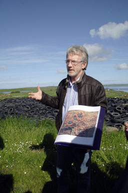 Abbildung: Archäologe Nick Card erzählt über die neolithische Zermonialstätte Ness of Brodgar, Grabungsfläche im Hintergrund / © Anita Soós