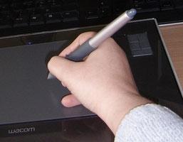 Ma main, tenant le stylet pour dessiner sur la tablette graphique
