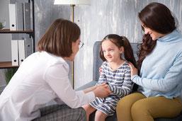 Enfant soutenue par sa maman dans la démarche d'intégration des réflexes archaïques, en face d'une praticienne en Intégration Motrice Primordiale