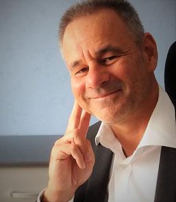 Dirk Feldhinkel sitzend, schaut Sie an und hört zu!